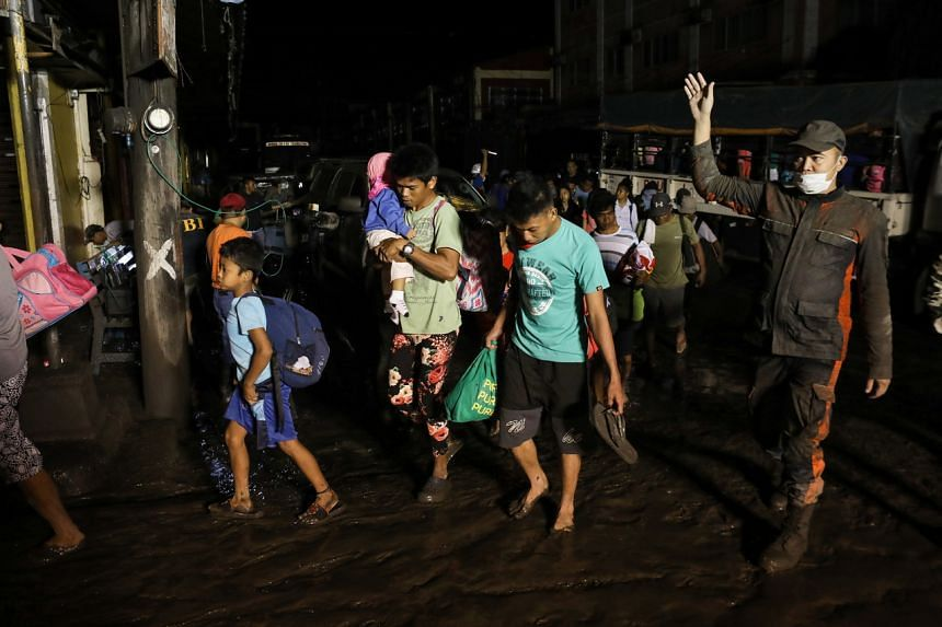 Villagers prepare to board rescue vehicles after a volcano eruption in the Philippines on Jan 13, 2020.