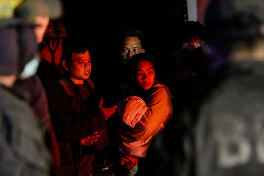 A woman holds on to her child before boarding a rescue vehicle after a volcano eruption in Talisay, Batangas, the Philippines on Jan 13, 2020.