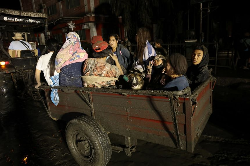 Villagers ride a tractor after a volcano eruption in Talisay, Batangas, Philippines on Jan 13, 2020.