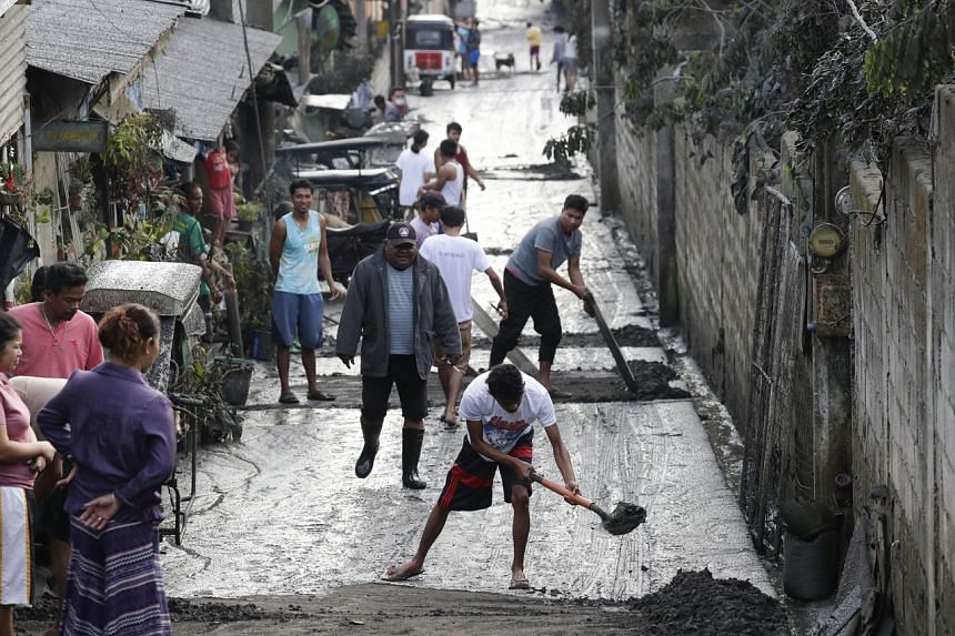 Residents clean ash from Taal volcano outside their homes in Tagaytay, Cavite province, south of Manila, Philippines on Jan 13, 2020.