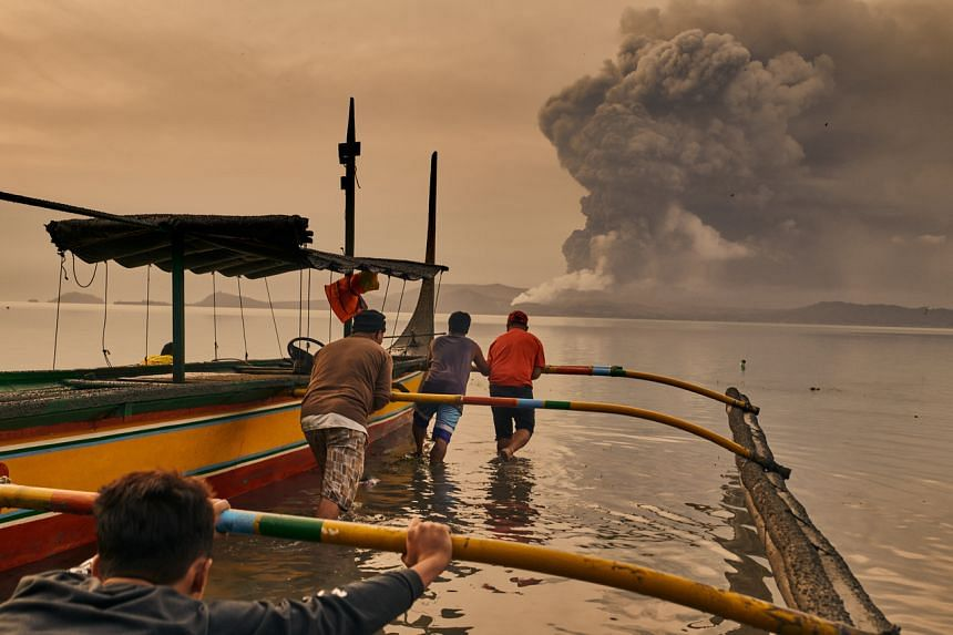 Residents prepare their boats to evacuate while the Taal Volcano erupts in Talisay, Philippines on Jan 13, 2020.