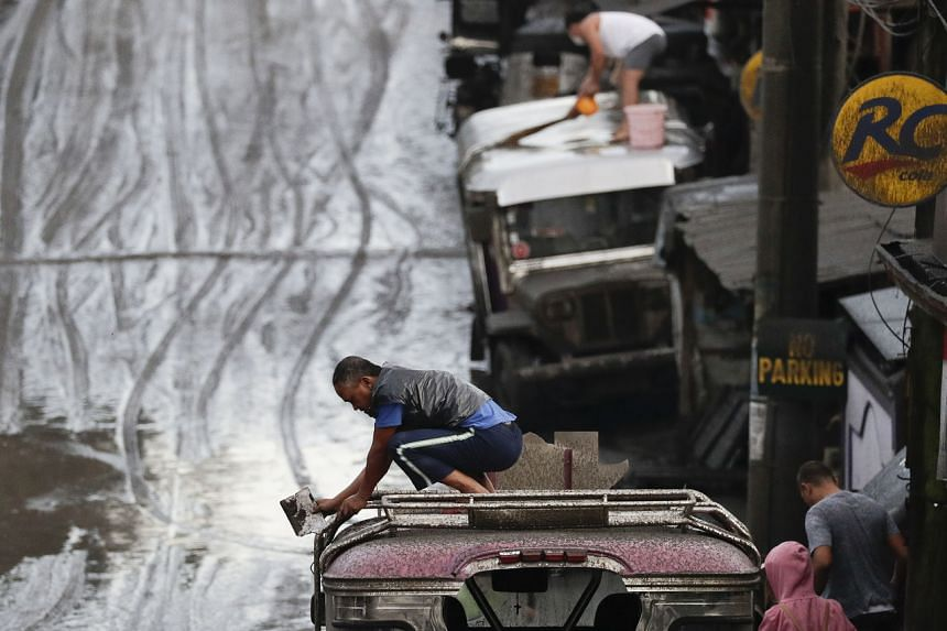 Residents clean ash from their vehicles after Taal volcano's eruption in Tagaytay, Cavite province, south of Manila, Philippines on Jan 13, 2020.