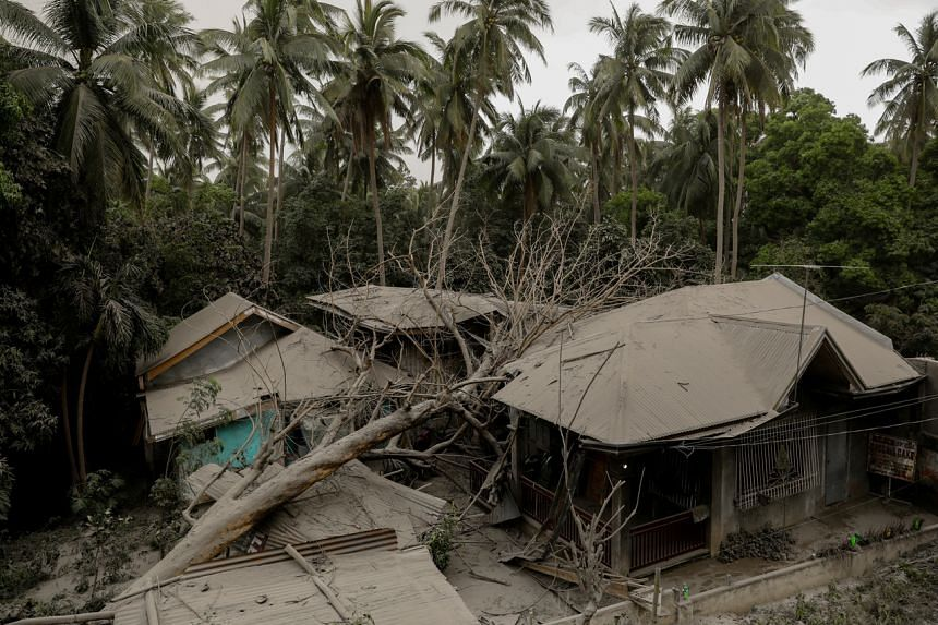 A house covered with ash, is damaged by a fallen tree in Lemery, Batangas City, Philippines on Jan 13, 2020.