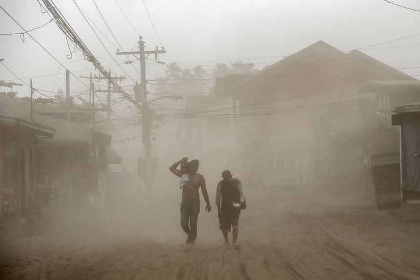 Residents living in Agoncillo, Batangas City, near the erupting Taal volcano, evacuate on Jan 13, 2020.