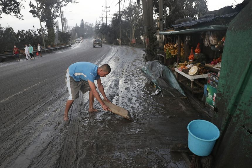 Residents clean ashfall from Taal volcano's eruption in Tagaytay, Cavite province, south of Manila, Philippines on Jan 13, 2020.