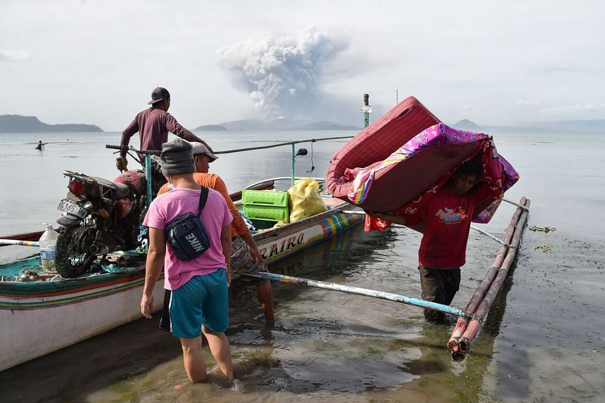 Evacuating residents living at the foot of Taal volcano unload their belongings from an outrigger canoe while the volcano spews ash as seen from Tanauan town in Batangas province, south of Manila on Jan 13, 2020.
