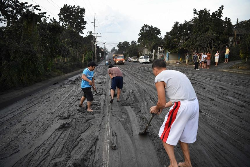 Residents help scrape a road covered with mud spewed by Taal volcano in Tanauan town, Batangas province south of Manila on Jan 13, 2020.