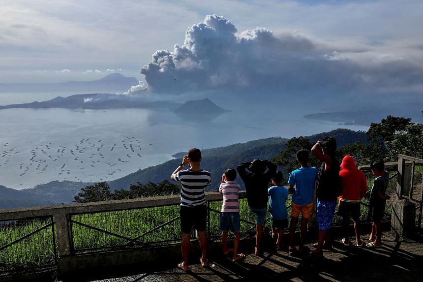 Residents look at the erupting Taal volcano in Tagaytay City, Philippines on Jan 13, 2020.