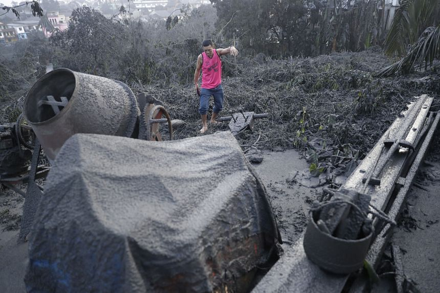 A man walks by ashfall-covered plants and equipment as Taal volcano continues to spew ash in Tagaytay, Cavite province, south of Manila, Philippines on Jan 13, 2020.