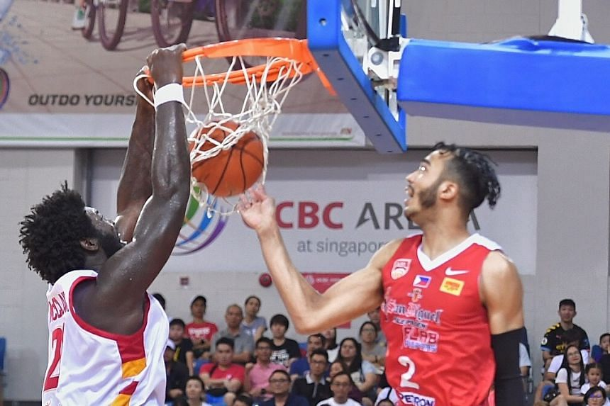 Slingers centre Anthony McClain dunking while Alab Pilipinas' Jeremiah Gray looks on at the OCBC Arena. Like Xavier Alexander, he was not happy with his previous outing and responded with 18 points yesterday.