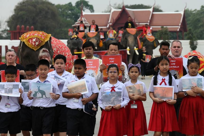 Thai children hold photos showing the damage caused by bushfires in Australia while domesticated elephants hold placards reading 'Pray For Australia' at an elephant camp in Ayutthaya, Thailand,  on Jan 13, 2020.