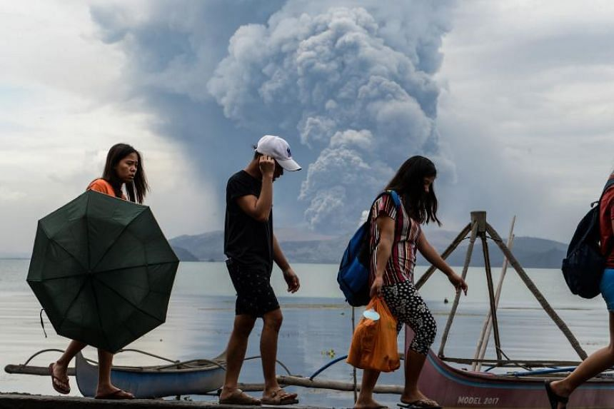 Residents walking past wooden boats in Tanauan town, Batangas province, as Taal volcano erupts on Jan 13, 2020.