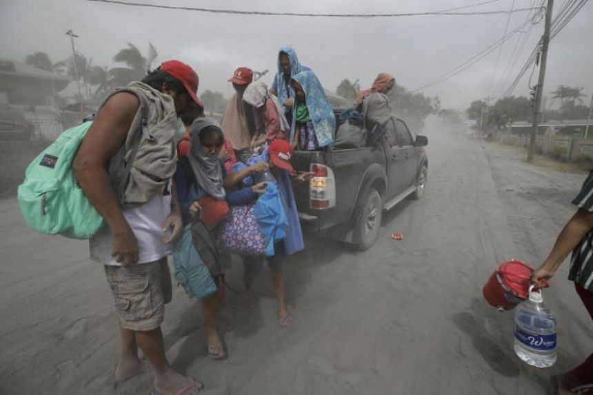 A family evacuates to safer grounds after an eruption of the Taal volcano on Jan 13, 2020.
