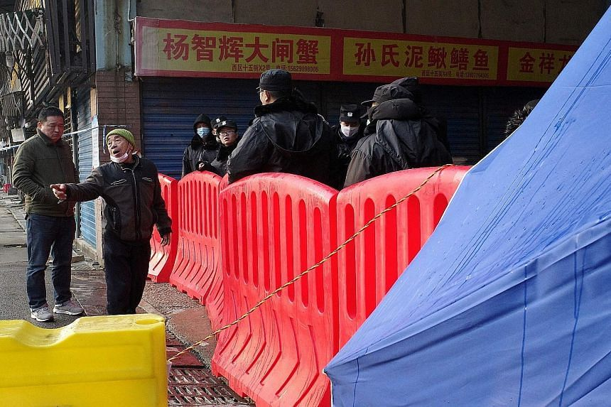 Right: A trader outside the closed Huanan wholesale seafood market in Wuhan. Below: The market sells seafood, live animals and meat from wildlife, leading to concerns that an infectious respiratory pathogen from animals had emerged. PHOTOS: AGENCE FR