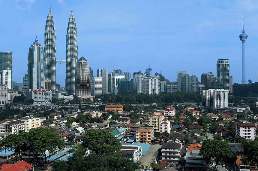 Kampung Baru sits beneath the Kuala Lumpur city skyline with the Petronas Twin Towers and KL Towers looming above it. The sprawling 120-year-old village comprises old village houses and ageing apartments. PHOTO: BLOOMBERG A model of the new Kampung B