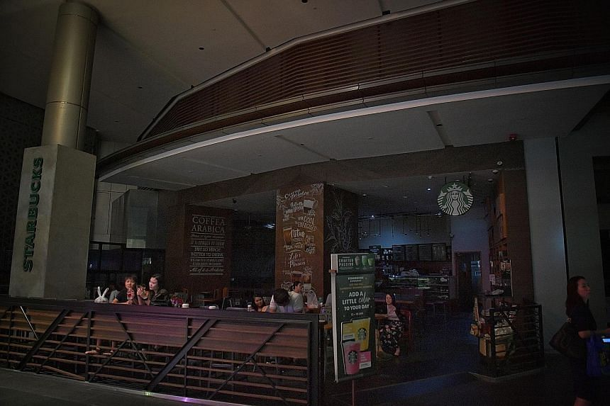 Patrons at the Starbucks outlet (left) at Raffles City last night. At 9.25pm, power had not yet been fully restored and much of the mall (below) was still in darkness.