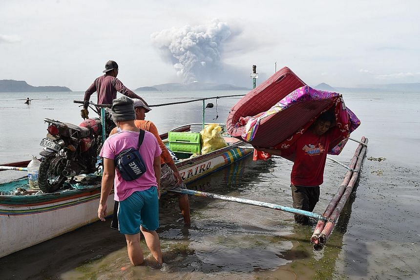 Residents unloading their belongings from a canoe in the town of Tanauan. More than 25,000 people have been evacuated to safer areas, most of them from Batangas province, which yesterday declared a state of emergency. A teenager living at the foot of
