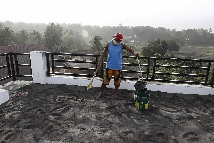 A resident sweeping up ash that had accumulated on the roof of his home in Agoncillo town, in Batangas province, yesterday.