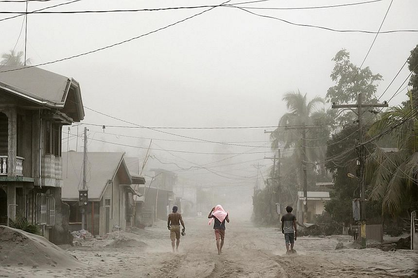 Residents living in Agoncillo, Batangas City, near the erupting Taal volcano, making their way through ash-covered streets yesterday.