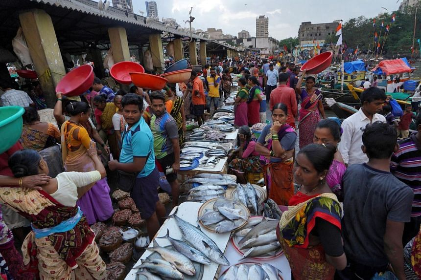 Vendors wait for customers in a wholesale market at a fish harbour in India on Nov 8, 2019. At the heart of India's problems is a slump in consumption following a combination of policy missteps.