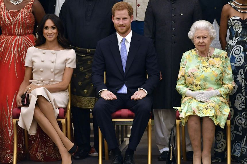 In a file photo taken on June 26, 2018, (from right) Britain's Queen Elizabeth, Prince Harry and Meghan, pose for a group photo at Buckingham Palace in London.
