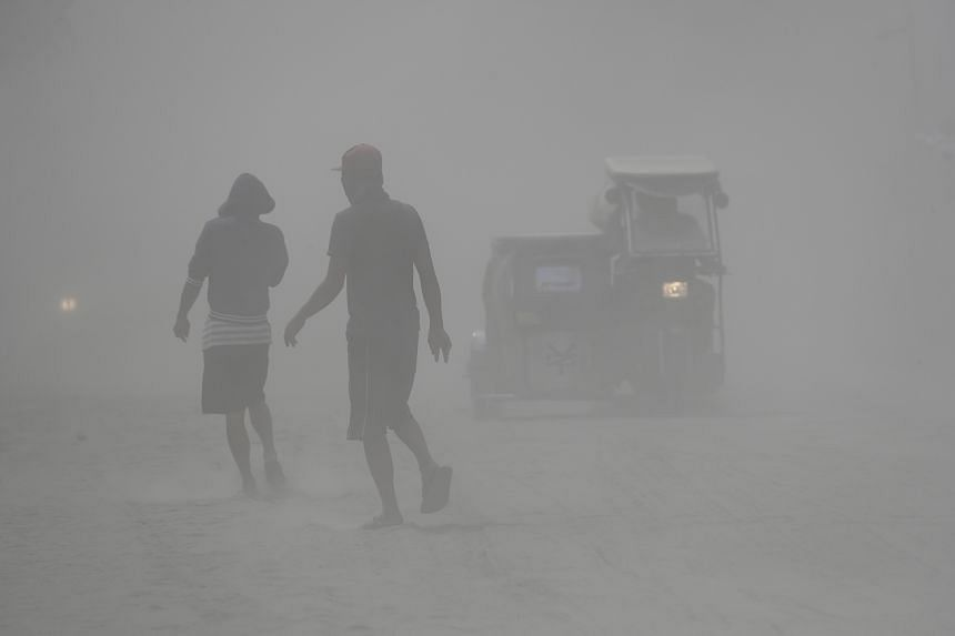 Residents walk in a cloud of ash as Taal Volcano continues to spew ash on Jan 13, 2020, in Lemery, Batangas province, south of Manila, Philippines.