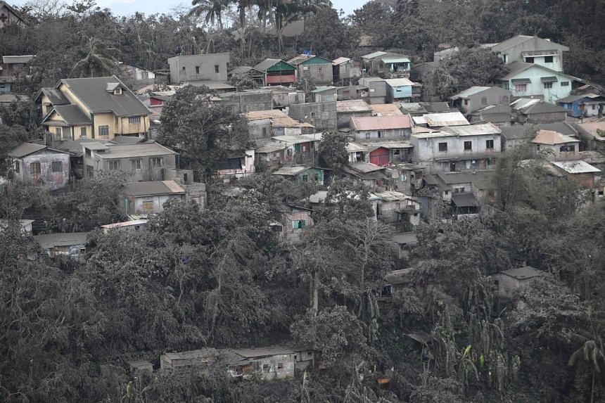 Houses with roofs covered with ash spewed by Taal volcano in Tagaytay City, Philippines, on Jan 14, 2020.