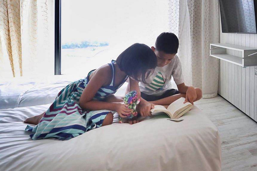 Children read a book together in a room.