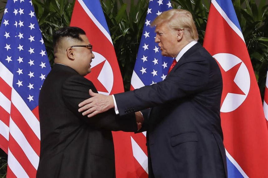 In this photo taken on June 12, 2018, US President Donald Trump shakes hands with North Korea leader Kim Jong Un at the Capella resort in Singapore.