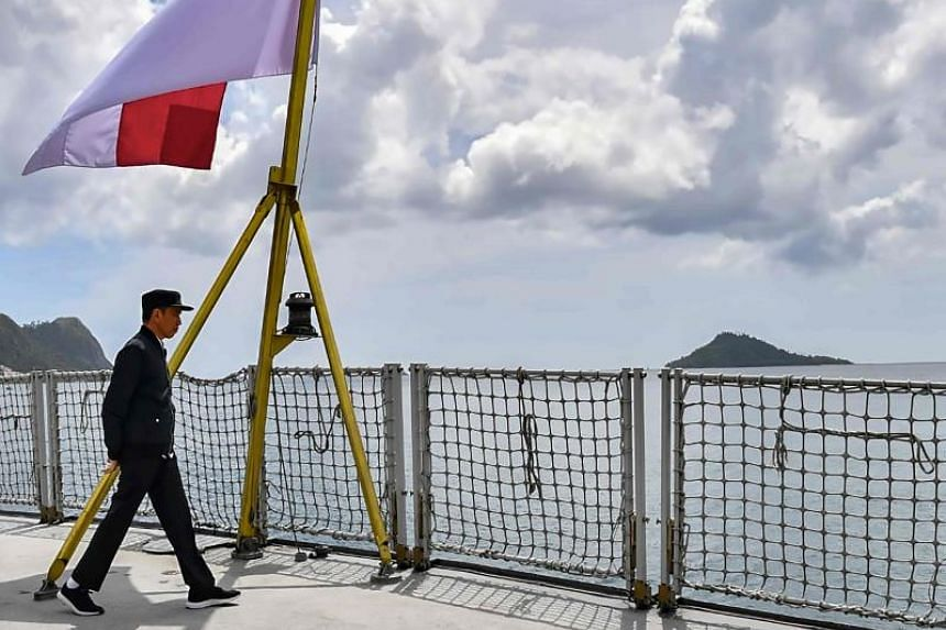 This photo taken on Jan 8, 2020, shows Indonesia's President Joko Widodo walking past the country's flag on a navy ship during his visit to a military base in the Natuna islands.