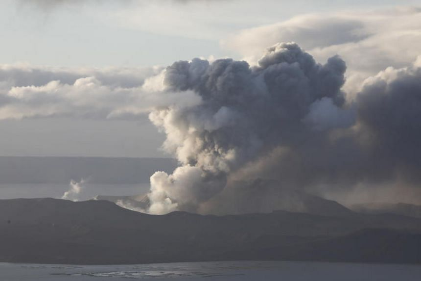 The Taal volcano spews steam and ash into the sky as seen from Tagaytay, Philippines, on Jan 2020.