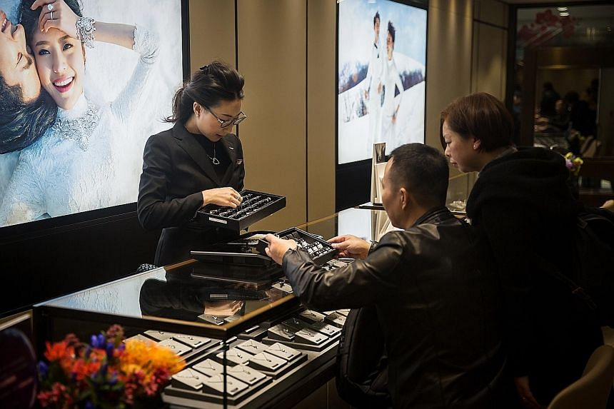 An employee showing jewellery to customers at a Chow Tai Fook store in Hong Kong, in a 2016 file photo. The jeweller plans to close about 15 of its Hong Kong stores, mainly in tourist districts.