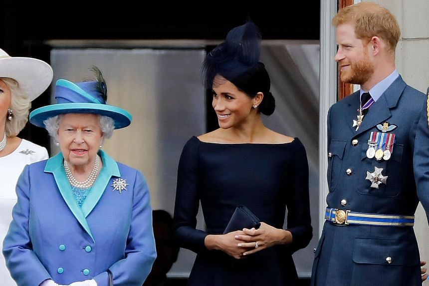 Queen Elizabeth with Prince Harry and his wife Meghan in a July 2018 photo. PHOTO: AGENCE FRANCE-PRESSE