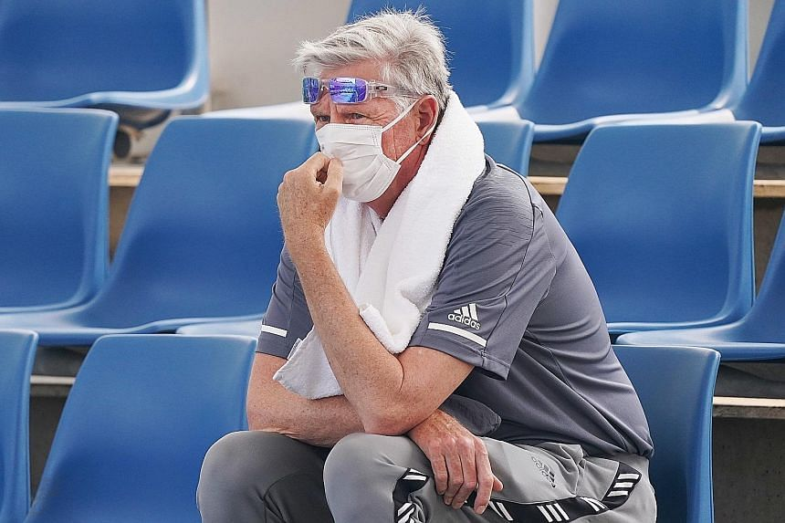 Left: Players have been struggling through their qualifying matches for the Australian Open at Melbourne Park with the air quality index reaching unhealthy highs. Above: The haze is affecting viewers in the stands as well, with this fan opting for a