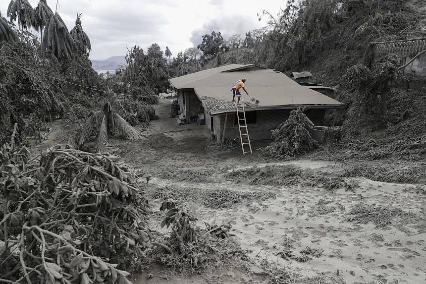 A man clearing volcanic ash from the roof of his house in Batangas province. Tens of thousands of people have fled villages blanketed by heavy ash from Taal.