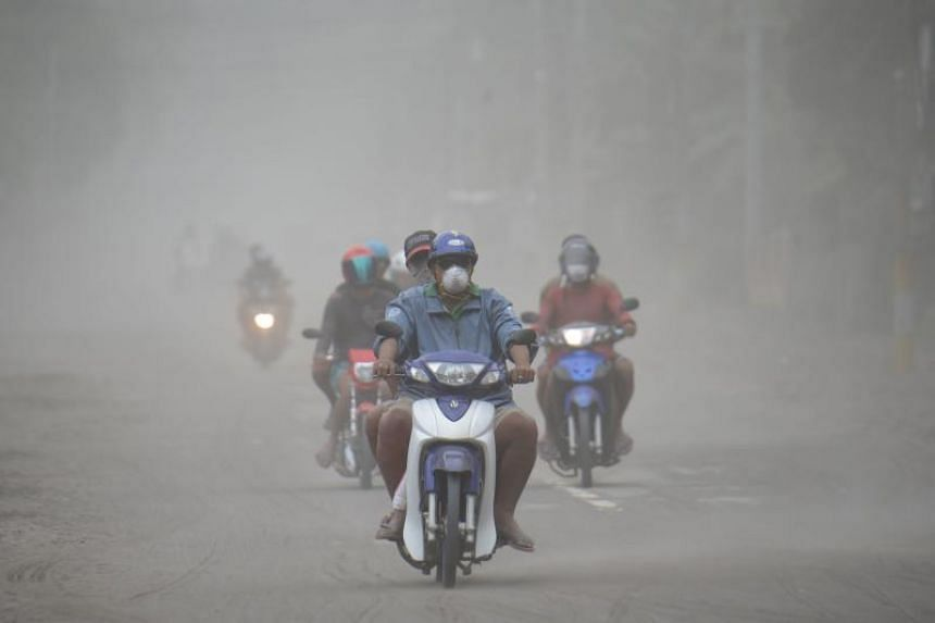 Volcano-affected residents ride along an ash-covered road as they return to evacuation centres after inspecting their homes in Agoncillo town, Batangas province south of Manila on Jan 15, 2020.