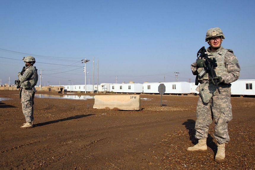 A 2014 photo shows US soldiers walking around at the Taji base complex in Iraq.