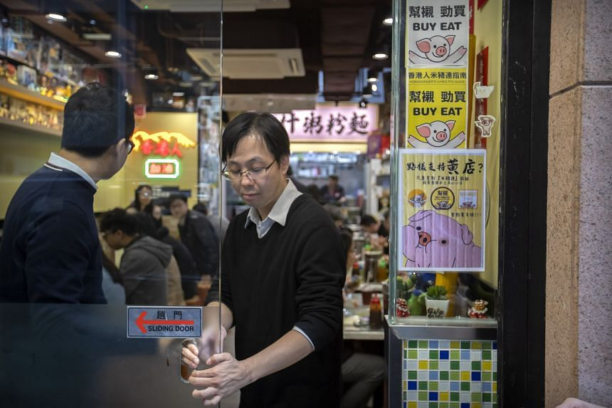 In a photo taken on Dec 13, 2019, a customer closes a sliding door at a restaurant decorated with pro-protest posters in Hong Kong.