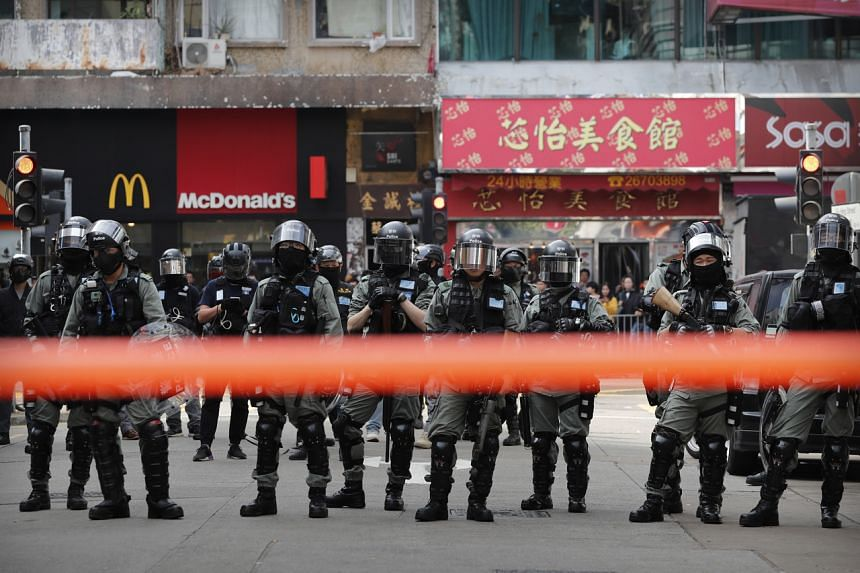 Riot police watch as protesters march during a demonstration in Sheung Shui, near the Chinese border, in Hong Kong, on Jan 5, 2020.