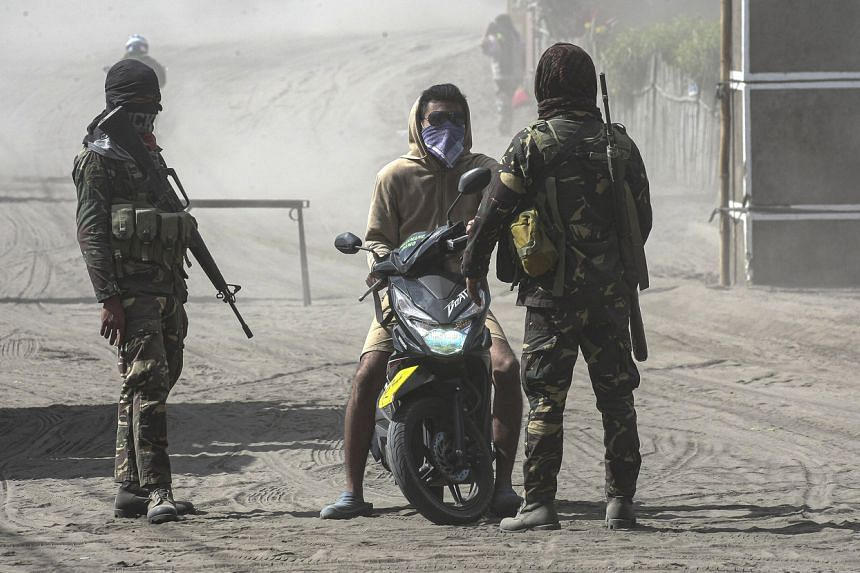 Philippine soldiers inspect a resident as they block roads going to the volcanic-ash covered town of Agoncillo, Batangas province, southern Philippines, on Jan 14, 2020.
