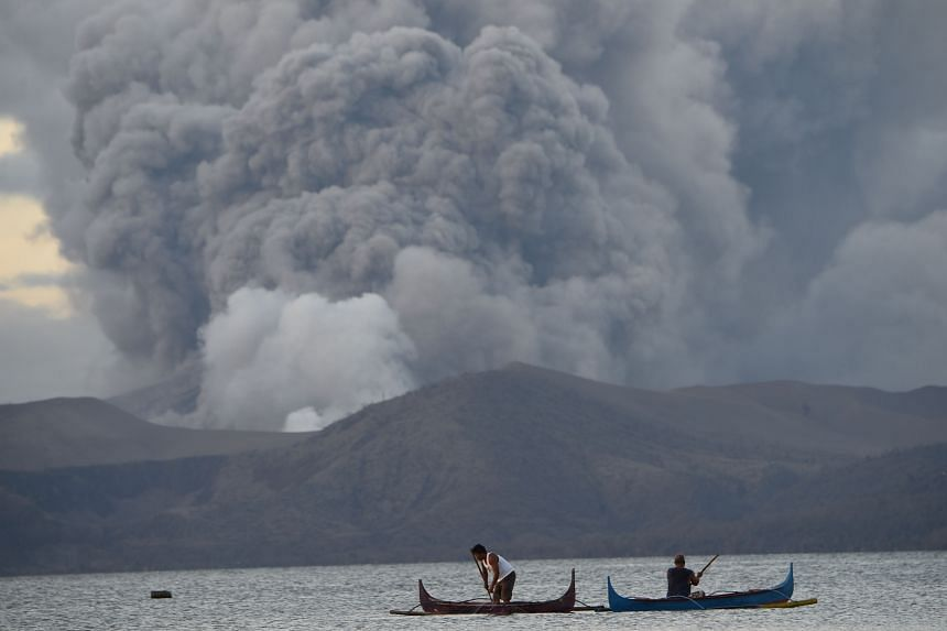 Residents living along Taal lake catch fish as the volcano erupts in Tanauan town, Batangas province south of Manila, on Jan 14, 2020.