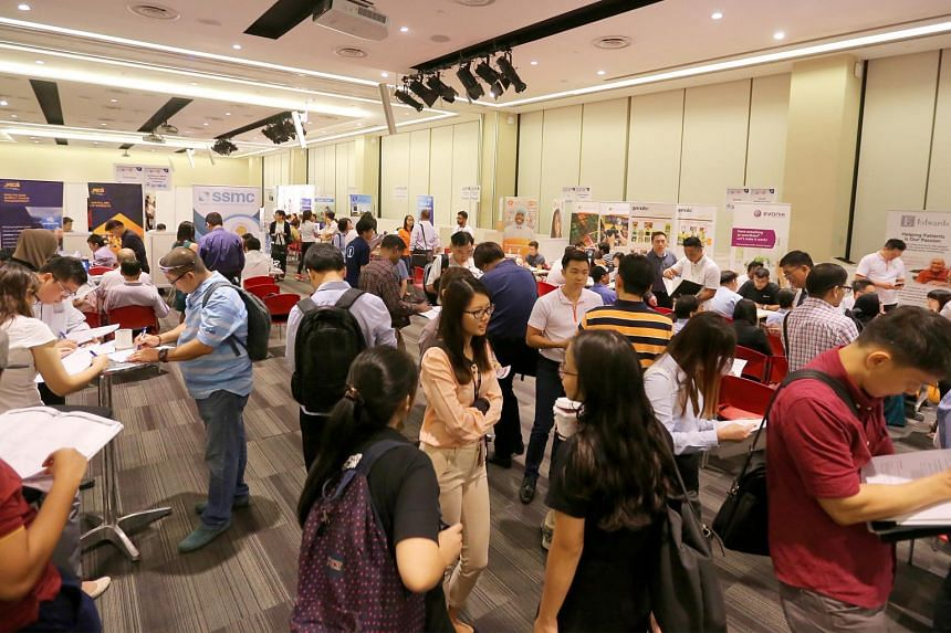 Job seekers attend a career fair at the Devan Nair Institute for Employment and Employability.