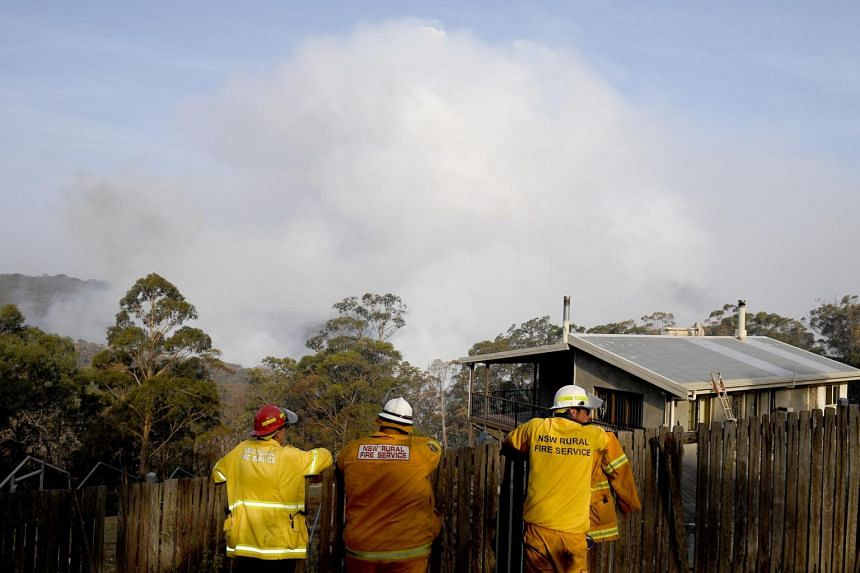 NSW Rural Fire Service crews watch on as the Morton Fire burns in bushland close to homes at Penrose in the NSW Southern Highlands, on Jan 10, 2020.
