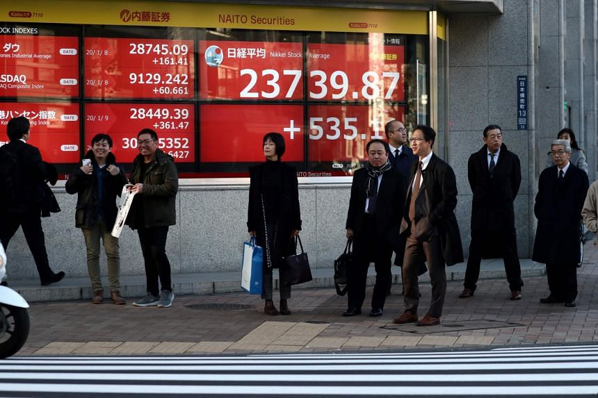People waiting to cross a street in front of a stock indicator displaying share prices of the Tokyo Stock Exchange, on Jan 9, 2020.