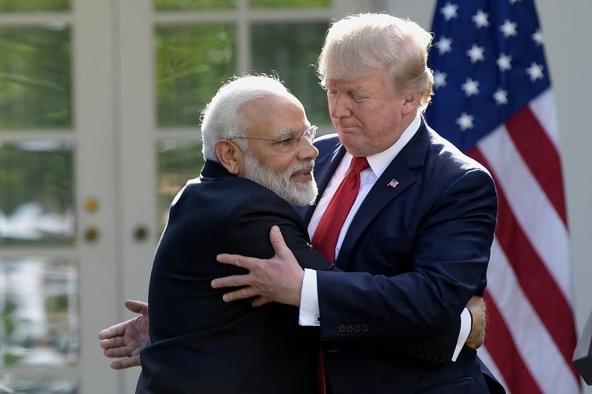 A 2017 photo ahows Trump (right) and Modi hugging at the White House.