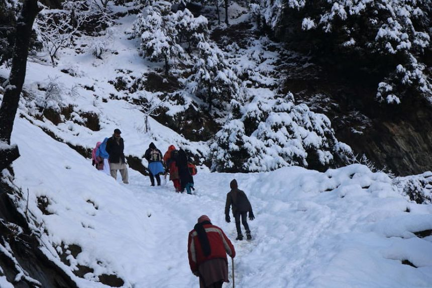People walk on a snow-covered mountain path in Neelum valley, Pakistani administered Kashmir, on Jan 14, 2020.