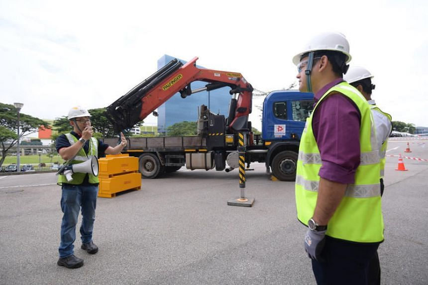 Minister of State for Manpower Zaqy Mohamad (foreground) during a demonstration of stability control system, which can detect the position of outriggers and compute the safe operating zone for cranes.