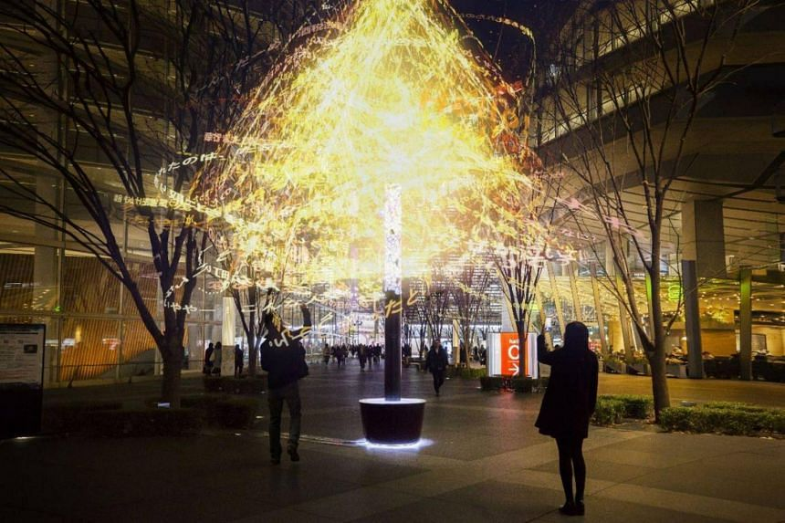 """Viewed through an app made by teamLab, the exhibit, titled Message Pillar - The Singapore Bicentennial becomes a virtual """"tree"""" with an augmented reality canopy of swirling messages."""