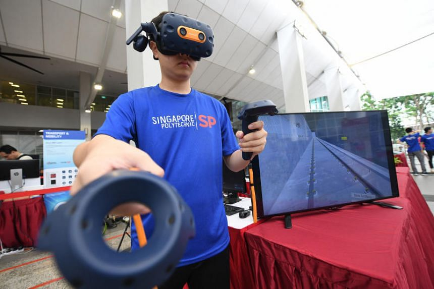 A Singapore Polytechnic student demonstrates a virtual reality training drill for SMRT staff, which simulates train track maintenance training.