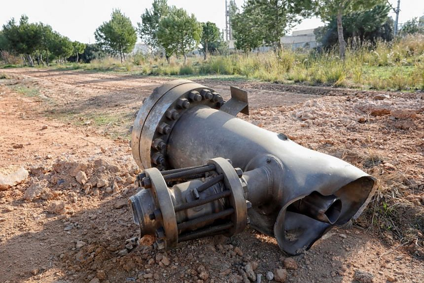 A piece of machinery projected by the chemical factory explosion lies in a field surrounding the area of the blast.